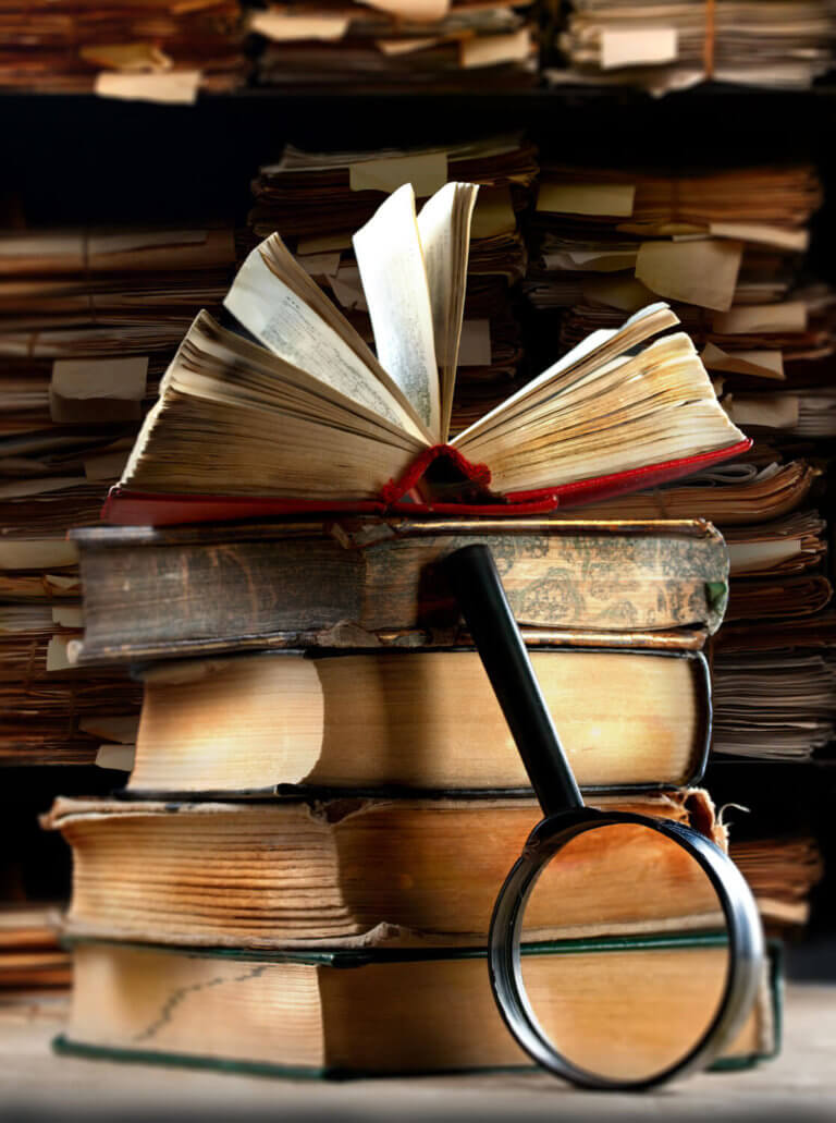 A stack of books with a magnifying glass